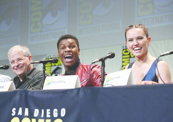 "SAN DIEGO, CA - JULY 10: (L-R) Screenwriter Lawrence Kasdan and actors John Boyega and Daisy Ridley at the Hall H Panel for ""Star Wars: The Force Awakens"" during Comic-Con International 2015 at the San Diego Convention Center on July 10, 2015 in San Diego, California.  (Photo by Jesse Grant/Getty Images for Disney) *** Local Caption *** Lawrence Kasdan; John Boyega; Daisy Ridley"